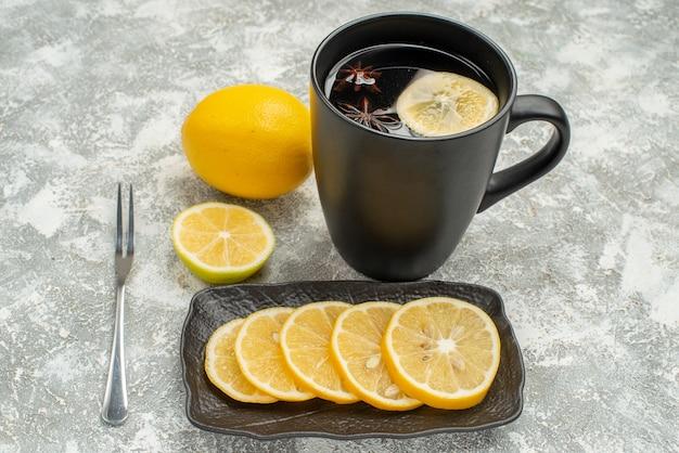 Vista lateral de cerca dulces negro taza de té con tenedor de limón anís estrellado
