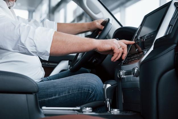 Vista lateral de cerca. empresario en ropa oficial se sienta en un automóvil de lujo y presiona los botones del reproductor de música