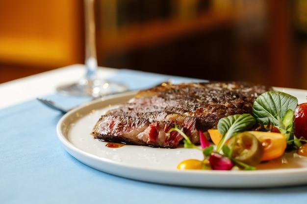 Vista lateral de cerca de filete de ternera chuletón en rodajas con ensalada de verduras frescas en la mesa azul