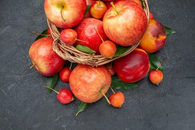 Vista lateral de cerca frutas frutos rojos-amarillos y bayas con hojas en la canasta de madera