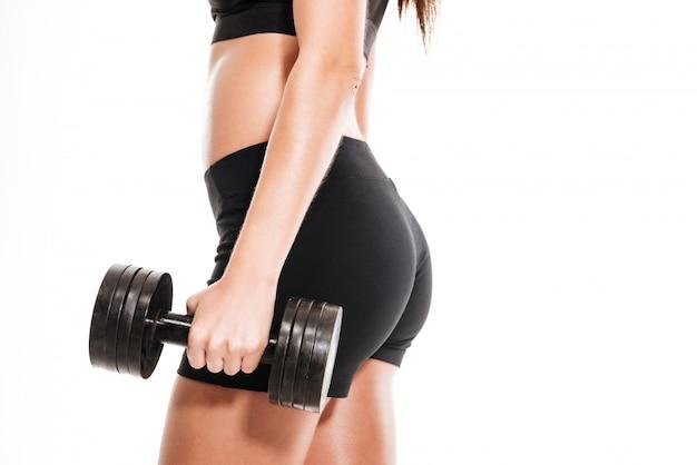 Vista lateral cerca de mujer deportiva con barra pesada