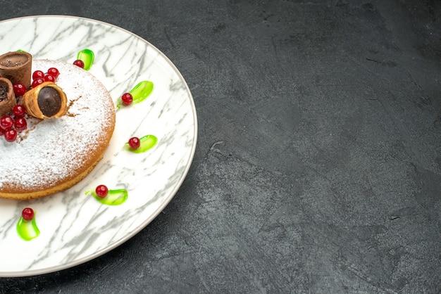 Vista lateral de cerca un pastel un pastel con frutos rojos azúcar en polvo waffles salsa verde