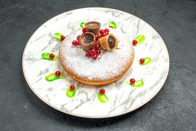 Vista lateral de cerca un pastel un pastel con gofres, bayas, azúcar en polvo, salsa verde