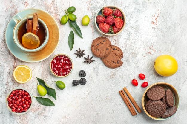 Vista lateral de cerca té con bayas galletas de chocolate la taza de té con limón y palitos de canela cuencos de bayas cítricos anís estrellado sobre la mesa