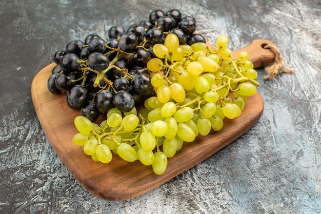Vista lateral de cerca las uvas las apetitosas uvas en la tabla de madera sobre la mesa