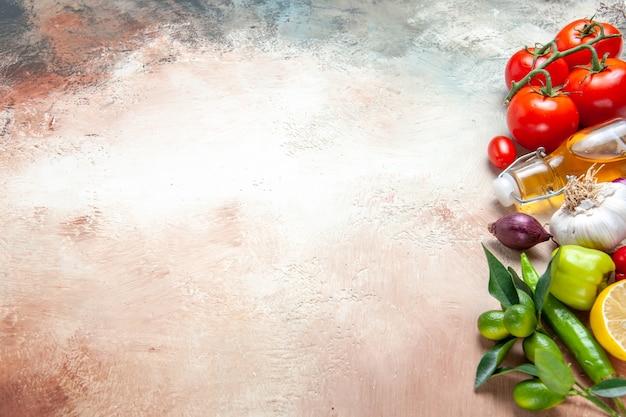 Vista lateral de cerca verduras aceite de limón cebolla ajo pimientos tomates con pedicelos