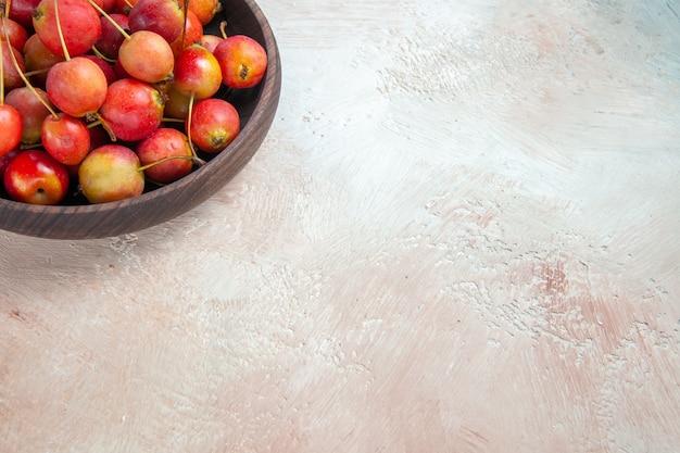 Vista lateral cercana cerezas cuenco marrón de las apetitosas cerezas en la mesa de color gris crema