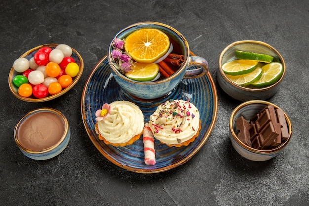 Vista lateral cercana cuencos de té de hierbas de chocolate en rodajas, crema de chocolate de lima y caramelos de colores junto a la taza azul de té de hierbas y dos cupcakes con crema sobre la mesa negra