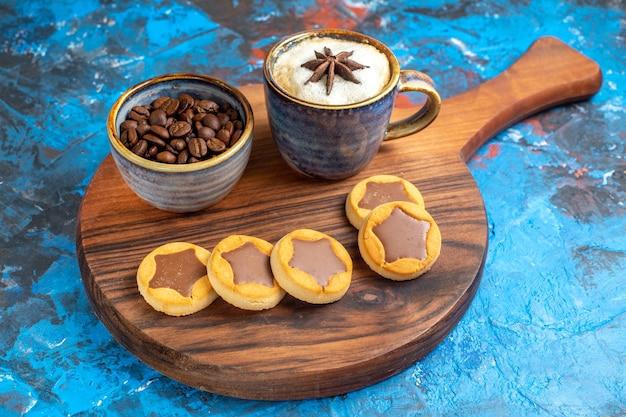 Vista lateral cercana dulces una taza de café, galletas y granos de café en el tablero