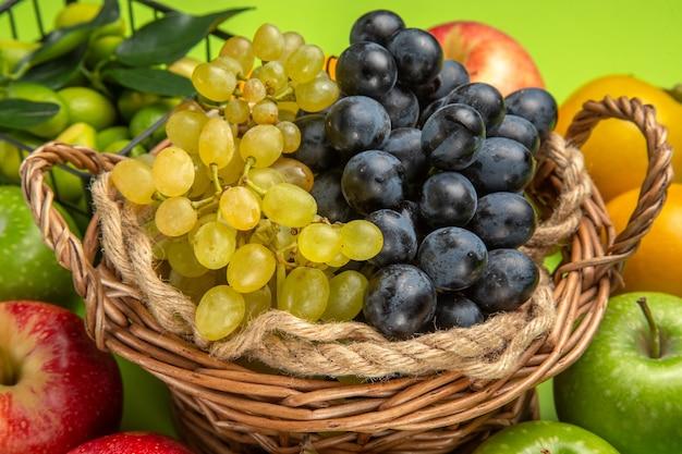 Vista lateral cercana frutas manzanas racimos de uvas caquis cítricos