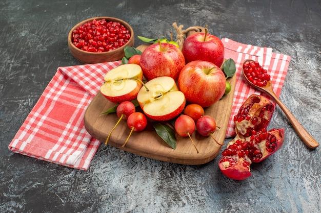 Vista lateral cercana granada manzanas cerezas en la tabla de cortar tazón de granada