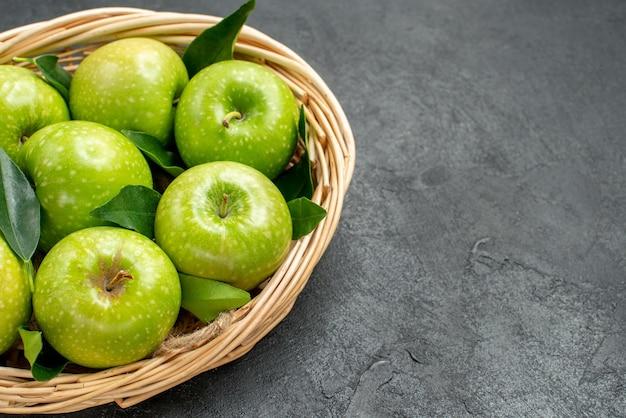 Vista lateral cercana manzanas en la canasta ocho manzanas con hojas en la canasta de madera