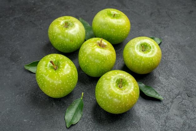 Vista lateral cercana manzanas verdes seis apetitosas manzanas verdes con hojas sobre la mesa oscura