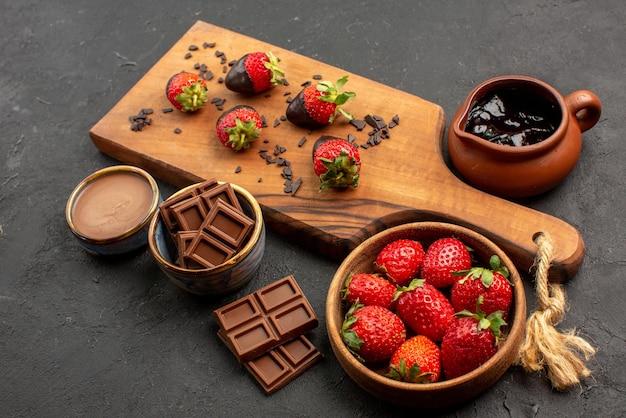 Vista lateral cercana de moras de chocolate a bordo de barras de fresas de crema de chocolate con chocolate en un tazón junto a fresas cubiertas de chocolate en la tabla de cortar de la cocina