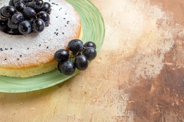 Vista lateral cercana de un pastel un apetitoso pastel con racimos de uvas azúcar en polvo en la placa