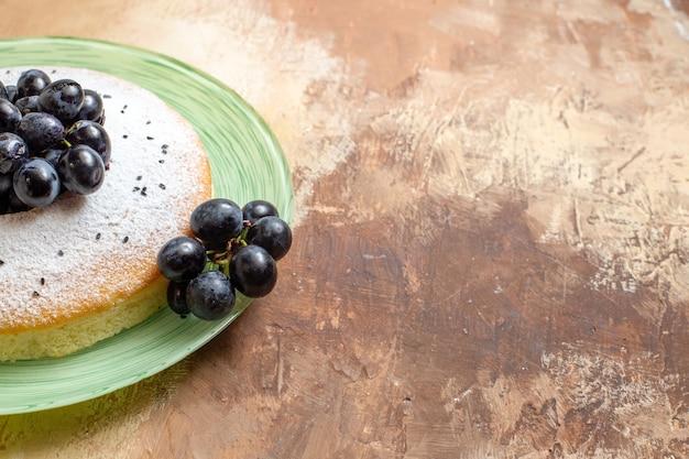 Vista lateral cercana de un pastel un apetitoso pastel con uvas y azúcar en polvo en el plato
