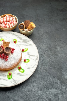 Vista lateral cercana un pastel un pastel con gofres grosellas rojas cuencos de dulces