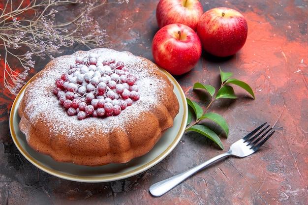 Vista lateral cercana pastel un pastel con grosellas rojas y azúcar tenedor manzanas hojas ramas