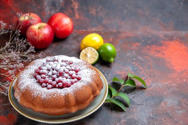 Vista lateral cercana pastel un pastel con grosellas rojas manzanas cítricos ramas de árboles hojas
