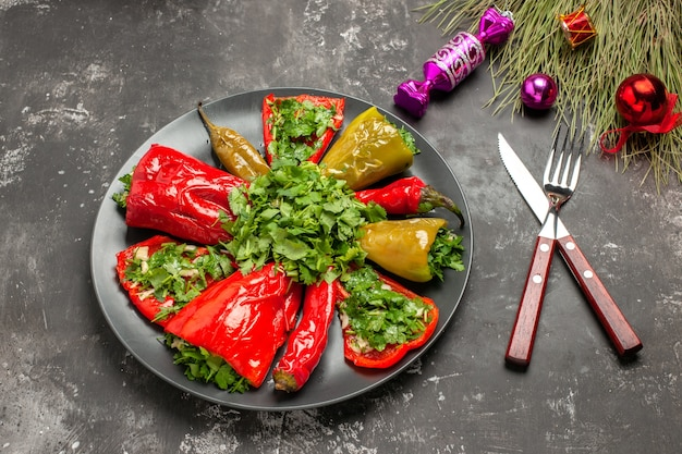 Vista lateral cercana plato pimientos con hierbas cuchillo tenedor caramelos juguetes de navidad