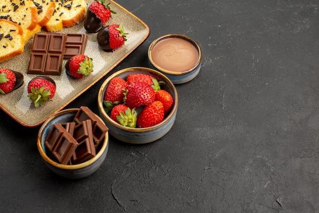 Vista lateral cercana postre apetitoso pastel con fresas y chocolate en placa gris junto a tazones con fresas y crema de chocolate en el lado izquierdo de la mesa