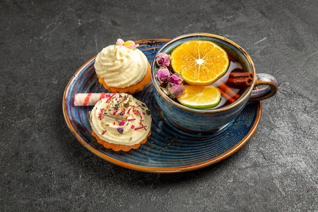 Vista lateral cercana de una taza de té con limón dos cupcakes con crema y dulces junto a la taza de té de hierbas con limón y canela en la mesa oscura