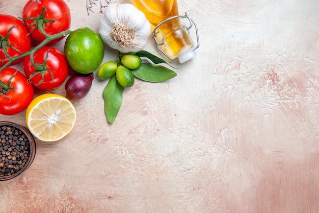 Vista lateral cercana tomates botella de aceite cítricos tomates cebolla ajo limón pimienta negra