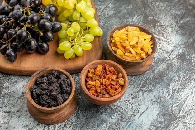 Vista lateral cercana uvas tazones marrones de frutos secos y racimos de uvas en el tablero de la cocina