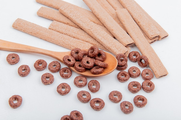 Vista lateral de cereales en cuchara de madera y galletas en superficie blanca