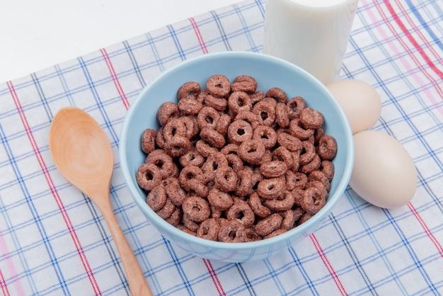 Vista lateral de cereales en un tazón con huevos de leche y cuchara de madera sobre tela escocesa y blanco