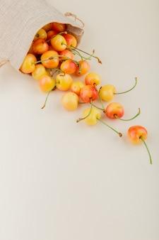 Vista lateral de cerezas amarillas derramándose de saco en superficie blanca con espacio de copia