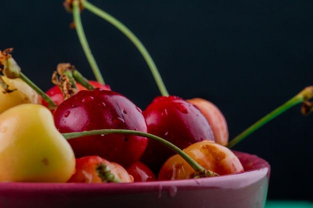 Vista lateral de cerezas maduras rojas y amarillas en un recipiente sobre superficie oscura