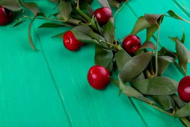 Vista lateral de cerezas maduras rojas con hojas verdes en madera verde