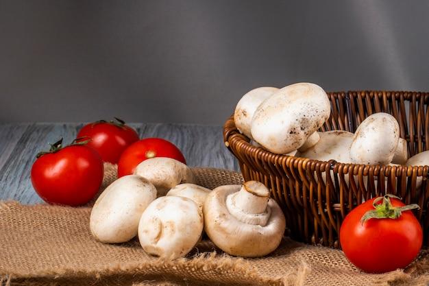 Vista lateral de champiñones champiñones frescos en una cesta de mimbre y tomates frescos en tela de saco
