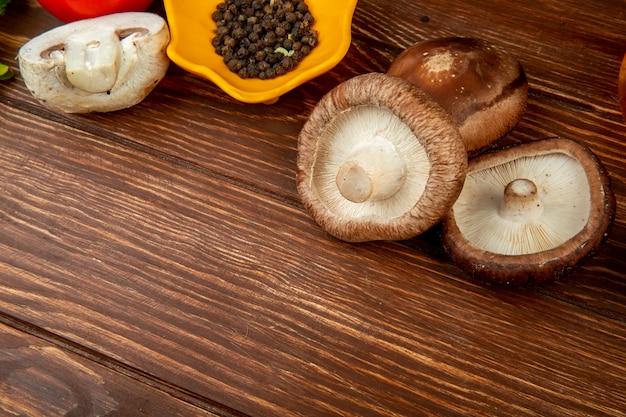 Vista lateral de champiñones frescos y granos de pimienta negra en madera rústica con espacio de copia