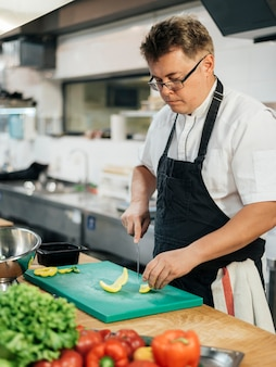 Vista lateral del chef cortando verduras