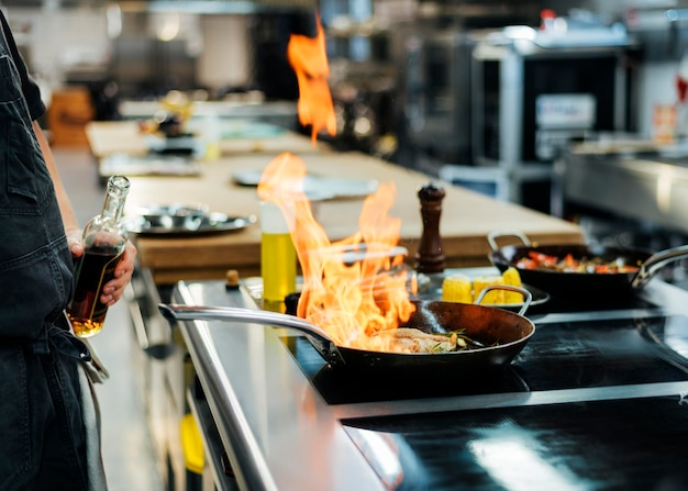 Vista lateral del chef flameando un plato en la cocina
