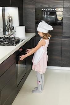 Vista lateral de la chica abriendo el horno mientras se hornea en la cocina