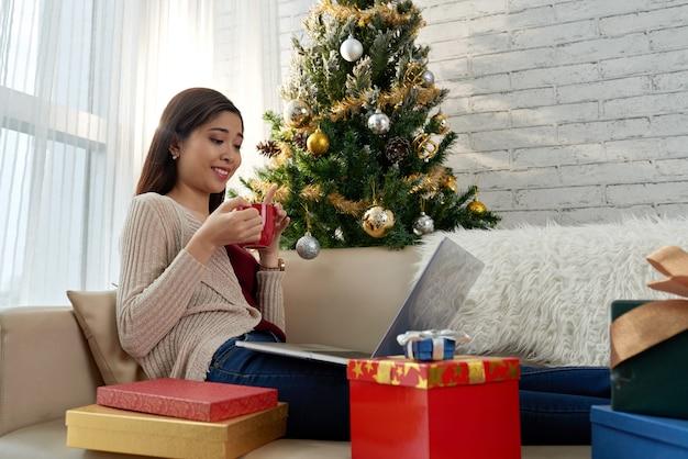 Vista lateral de una chica asiática comprando en línea en nochebuena