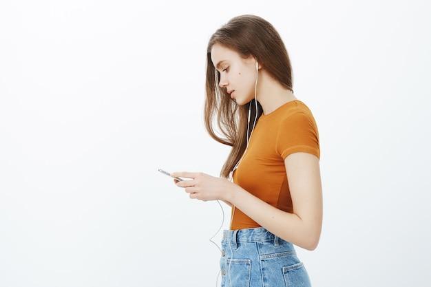 Vista lateral de una chica atractiva de aspecto serio con teléfono móvil en auriculares, escuchando música, viendo videos