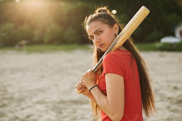 Vista lateral chica con bate de béisbol