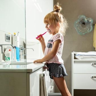 Vista lateral chica cepillarse los dientes en el baño.