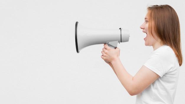 Vista lateral chica gritando en megáfono