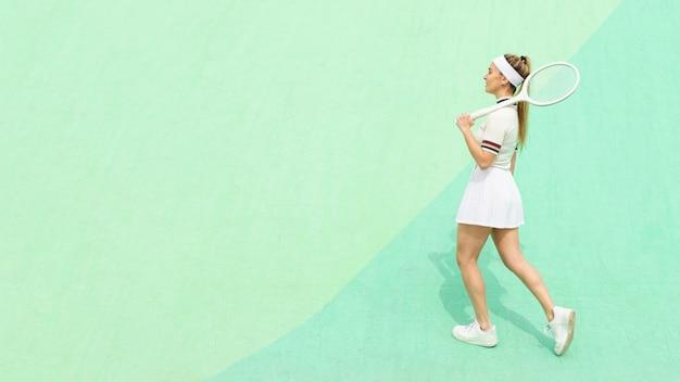 Vista lateral chica con raqueta de tenis en un campo de tenis