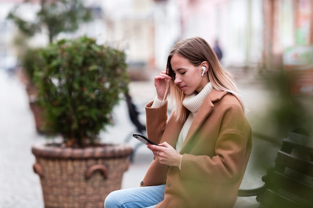 Vista lateral chica rubia escuchando música en auriculares