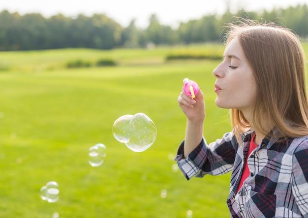 Vista lateral chica rubia haciendo burbujas