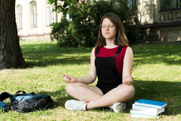 Vista lateral de la chica de secundaria meditando
