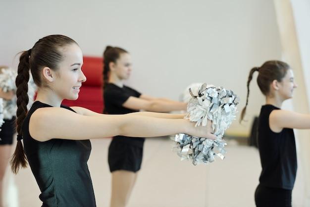 Vista lateral de chicas adolescentes positivas en trajes negros bailando con pompones en la competencia de porristas