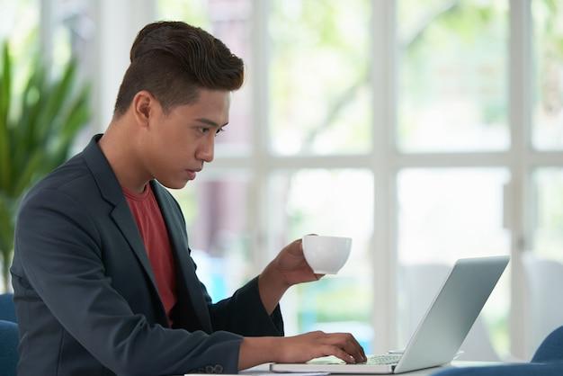 Vista lateral del chico asiático tomando café y trabajando en la computadora portátil