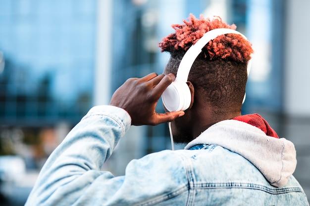 Vista lateral chico con auriculares y chaqueta de jeans